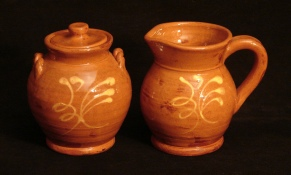redware sugar and creamer set with feather pattern